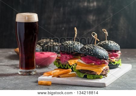 Gourmet black burger with berry sauce, french fries and beer on wooden table and dark background