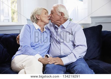Affectionate Senior Couple Sitting On Sofa At Home
