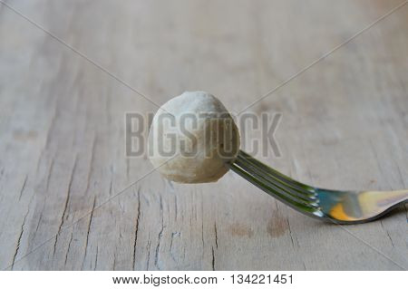 pork ball stab in fork on wooden board
