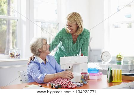 Senior Mother And Adult Daughter Use Sewing Machine At Home
