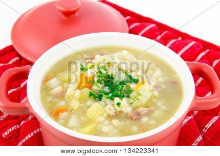 Barley soup with parsley in a red pot