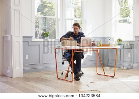 Man At Home Addressing Package For Mailing