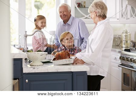 Children And Grandparents Make Roast Turkey Meal In Kitchen