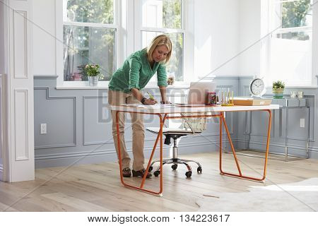 Woman Standing At Desk Working At Laptop In Home Office