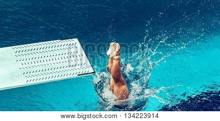 Female diver jumping from platform high angle view