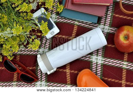 Individual objects lying on a red rug. Books thermos glasses case smartphone apple flowers