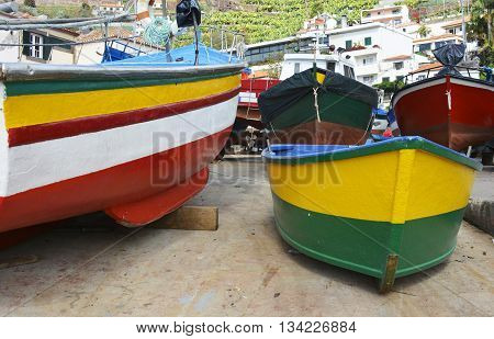 Newly painted red yellow and green fishing boats at Camara de Lobos in Madeira Portugal