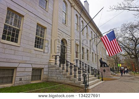 Cambridge, USA - April 29, 2015: University Hall and John Harvard Monument in the campus of Harvard University of Cambridge Massachusetts MA USA. It is a well-known statue of the University founder in America. Tourists in the yard