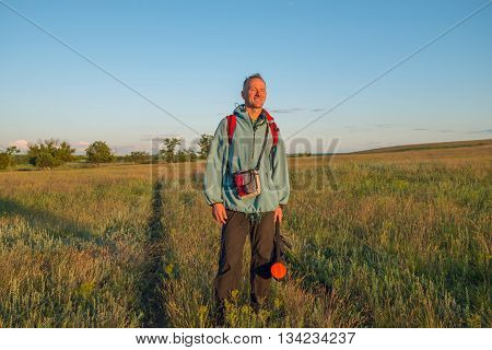 Happy hiker man stands in the prairie looking into the distance and smiling. Sunset in a prairie desert. Azov steppes Ukraine. Wide angle.