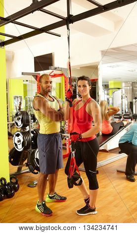 Fit man and woman standing in gym, ready for TRX suspension training.