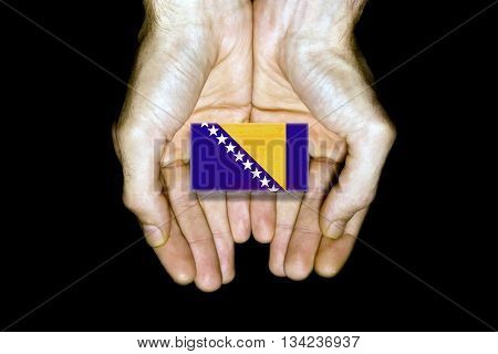 Flag of Bosnia and Herzegovina in hands isolated on black background.