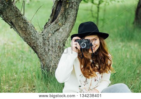 Wearing a white sweater and black hat in blooming garden. Beautiful young woman with long wavy hair thin slender figure perfect body and pretty face natural make-up. Photographer making pictures.
