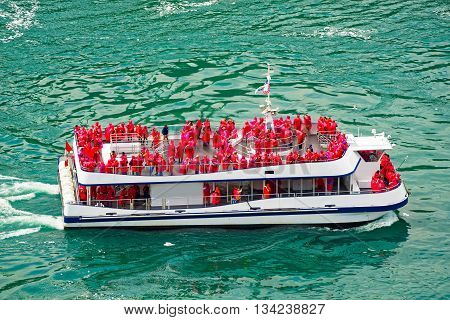 Niagara Fall, USA - April 30, 2015: Ferry in the Niagara River. A view from American side. Niagara River is a river from Lake Ontario to Lake Erie. It is a natural border between Canada and the USA. Tourists on board