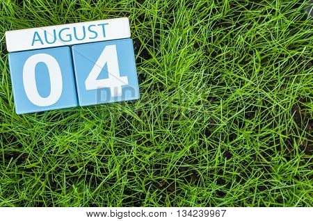 August 4th. Image of august 4 wooden color calendar on green grass lawn background. Summer day. Empty space for text.