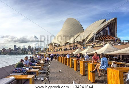 Tourists Sitting In Opera Bar In Front Of Sydney Opera House