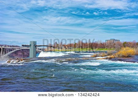 Niagara Falls, USA - April 29, 2015: Niagara Falls and Rainbow Bridge over Niagara River Gorge from American side. It is an arch bridge between the United States of America and Canada.
