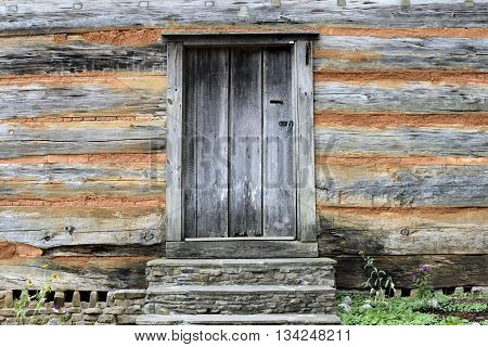 Old wood door at historic pioneer log cabin background