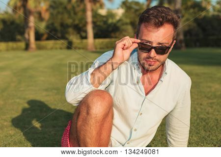 cool young man taking off his sunglasses while sitting on the grass in the garden