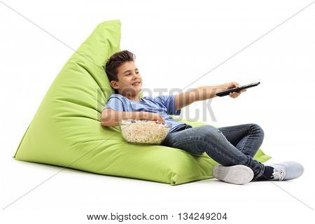 Little kid changing channels on TV and eating popcorn seated on a green beanbag isolated on white background