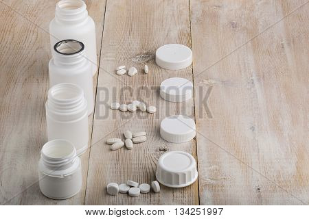 Various white plastic pill bottles and heap of drugs on bright wooden table