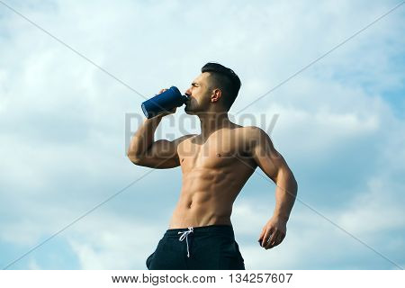 Young sexy man with muscular sexy body and bare torso with chest outdoor drinking water from bottle on sky natural background
