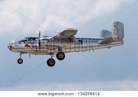 BERLIN - JUN 2 2016: Red Bull B-25 Mitchell WWII bomber plane landing on Berlin-Schoneveld airport