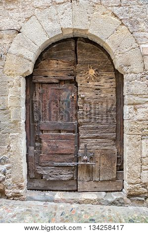 Antique wooden door in the medieval village of Besalu in Catalonia Spain.