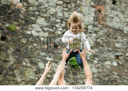 Parents playing with smiling baby girl in air with hands on stony wall background outdoor