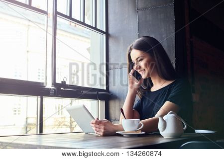 Young Girl Talking On Mobile Phone In Coffee Shop