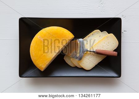 Black ceramic rectangle dishes with block of tasty cheese isolated on white wooden desk