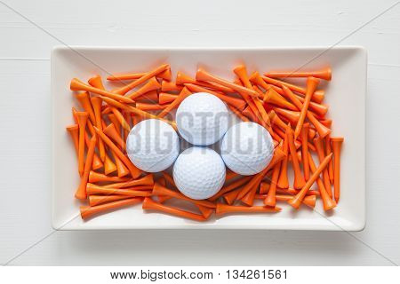 White ceramic dishes with golf balls and wooden tees on over white background rectangle dish