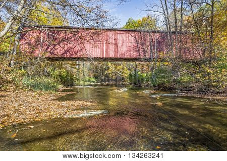 Fountain County Indiana's Rob Roy Covered Bridge built in 1860 crosses Big Shawnee Creek surrounded by autumn colors.