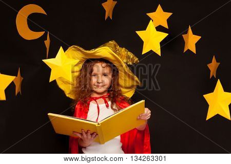 Little girl in sky watcher costume studying constellation of stars, holding big book with copy space at the night sky background