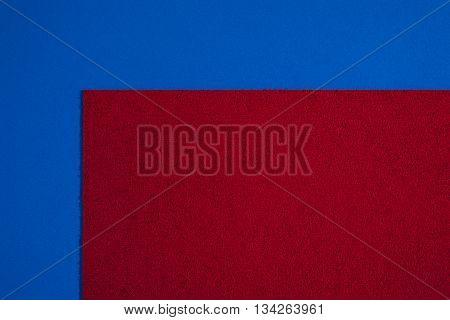 Eva foam ethylene vinyl acetate sponge plush red surface on blue smooth background
