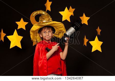 Five years old boy in sky watcher costume with telescope among handmade paper stars