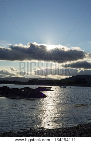 boats in a quiet bay near kenmare on the wild atlantic way ireland with a cold sunset