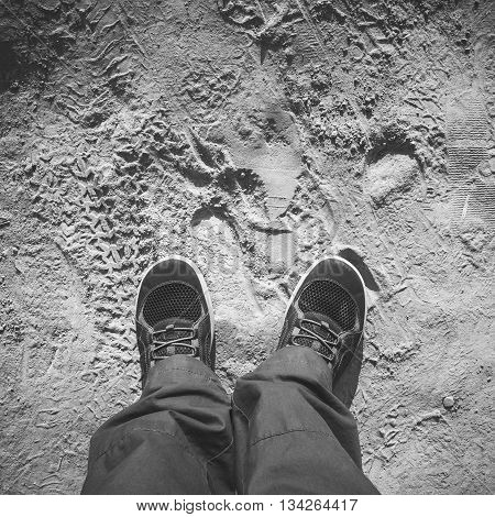 Male Feet In Shoes Stand On Dirty Dusty Road