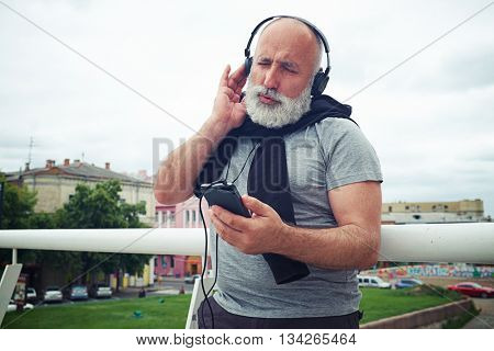 Stylish aged man in headphones stands near handhold on the bridge and enjoys music from his smart phone