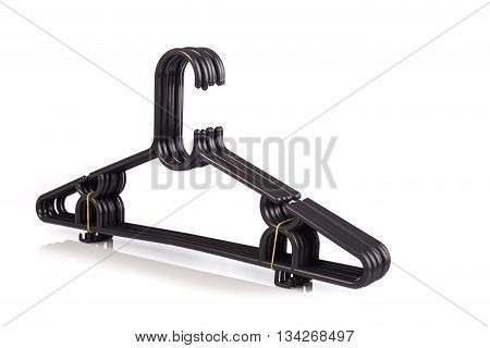 Close Up Pack Of New Black Clothes Hanger Isolated On White .