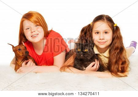 Two little girls red and brown lay on the fur with dog and cat on white background