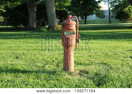 A red old style fire hydrant in a park near Building 50 close to Traverse City, Michigan.