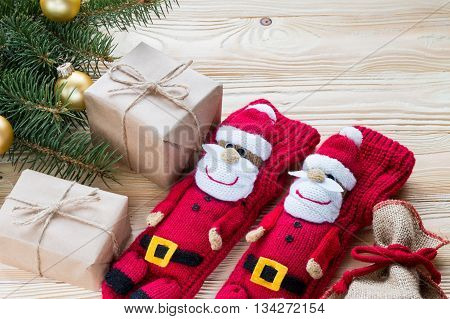 knitted Christmas Stockings as Santa Claus christmas gifts packaged in kraft paper jute rope constricted on wooden table with Christmas tree . top view free space for text