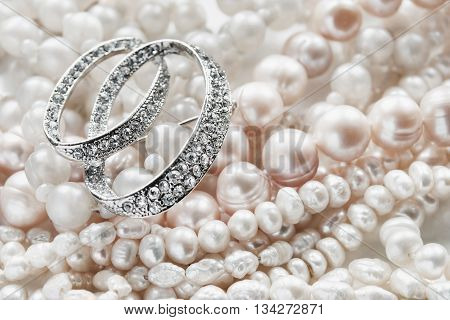 Diamond brooch and strings of pearl closeup as a background