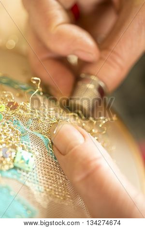 Hands stitching gold-threaded embroidery on a tambour poster