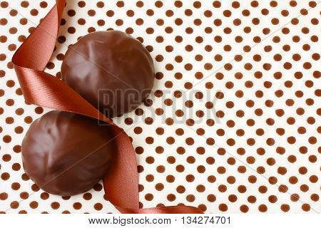 Zephyr in chocolate lying on tablecloth with polka dots silk ribbon retro style