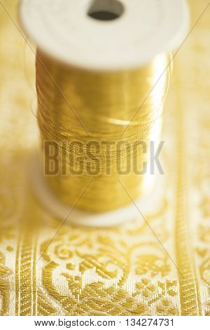 A spool of gold-colored thread on embroidered fabric