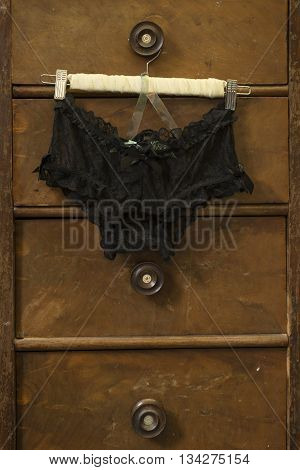 A pair of black velvet knickers pinned to a clothes hanger and hung on a drawer handle.