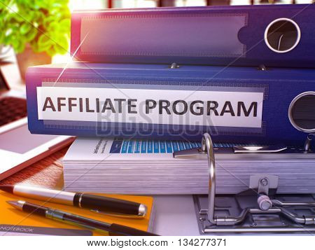 Blue Ring Binder with Inscription Affiliate Program on Background of Working Table with Office Supplies and Laptop. Affiliate Program Business Concept on Blurred Background. 3D Render.