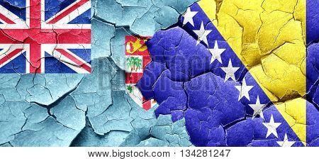 Fiji flag with Bosnia and Herzegovina flag on a grunge cracked w