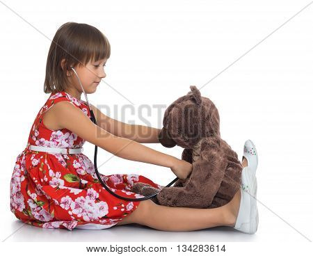 Dressy little girl playing with a Teddy bear in the hospital . the girl Listens to the bear stethoscope - Isolated on white background